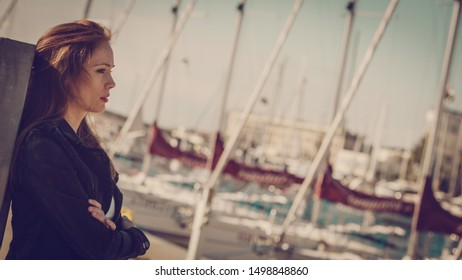 Nostalgic woman walking around jetty pier wearing black jeans jacket. Female fashion model during spring weather, having long brown hair wind tousled.