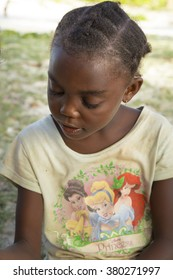 Nosy Iranja, Madagascar - November 7, 2015: Malagasy kid portrait with an old yellow Disney shirt on a tropical beach background