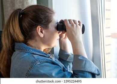 Nosy woman peering through window with binoculars, domestic room