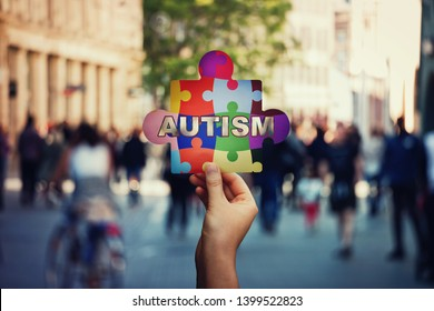 I am not alone symbol of Autism as a child hand holding a colorful puzzle piece over a crowded street background. Social awareness, autistic education development. Jigsaw fragments connected together.