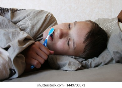 Not available to get up in the morning concept. Teenager young caucasian boy can not wake up and he is cleaning his teeth with a toothbrush lying in bed.