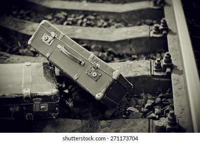 Not the color image of two old suitcases on railway rails.