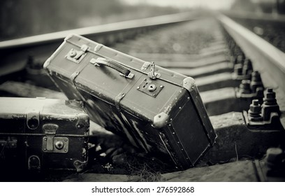 Not the color image of two old forgotten suitcases on rails.