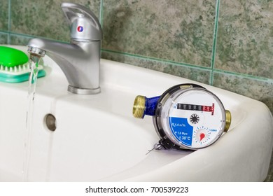 Not connected residential water meter for consumption measuring of a cold water on a wash basin on background of a water flowing from handle mixer tap and wall with green tiles