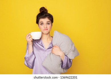 It's not easy to wake up. Waist up portrait of annoyed sleepy brunette female in silk pajamas staying with coffee and pillow. Isolated on yellow