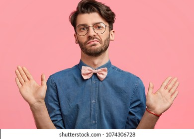 I am not guilty! Fashionable bearded guy being hesitant or shows his non participation in something, has bristle, wears stylish denim shirt, isolated over pink studio background. Body language