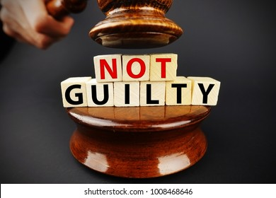 Not guilty verdict or court decision with judge gavel on dark background