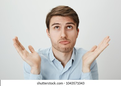 I am not involved, this hands are pure. Indoor portrait of handsome confused guy shrugging with raised palms, looking up and puckering as if making mistake and having no clue how to fix it