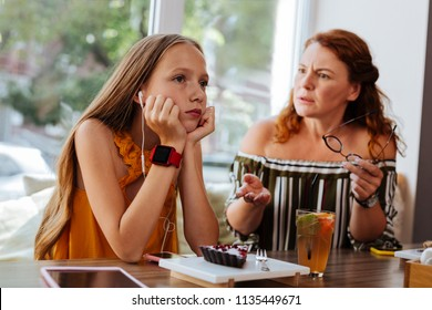 Not listening. Blonde-haired teenager using earphones pretending not listening to her angry mother