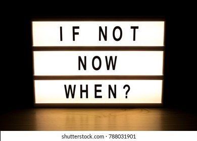 If not now when light box sign board on wooden table.