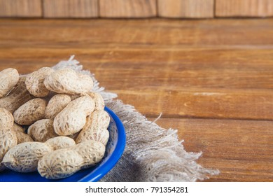 Not peeled peanuts in blue plate on sackcloth on wooden background