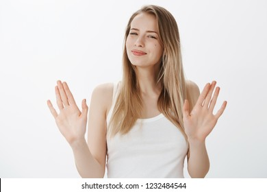 Not really into it. Portrait of woman refusing offer in polite manner smiling friendly wirh sorry look as waving hands in rejection gesture being ininterested and not in mood over gray background