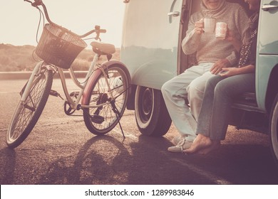 not recognizable couple of caucasian couple having fun and drinking coffee together sitting outside the old vintage van sith bike parked outdoor - sunset time and vacation alternative travel concept