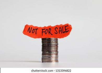 Not for sale campaign. 'NOT FOR SALE' message on the ripped paper on the pile of coins.