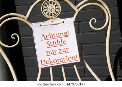 Not for sale. View on cardboard with red message on antique metal chair (German text Achtung! Stühle nur zur Dekoration meaning: Attention! Chairs only for decoration) - Germany