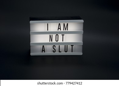 I Am Not a Slut text in a light box. Dark, isolated background. A sign with a message. Women shaming. Me Too movement