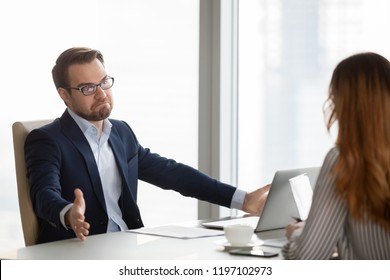 Not sure businessman at meeting with partners shrugs his shoulders in doubt. Man spreads his hands, do not like terms of deal, contract. Saying sorry, unsuccessful negotiations, not signing contract
