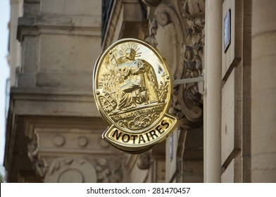Notaries french sign. France Republic official logo of notaries. Shiny gold sign on stone building.