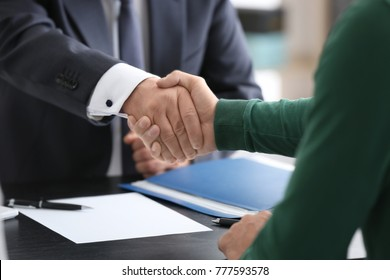 Notary and client shaking hands in office