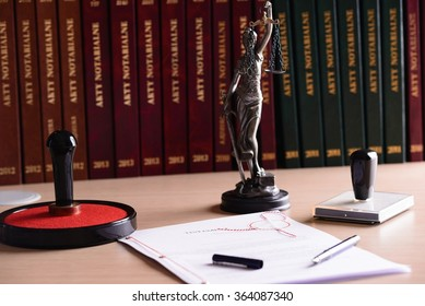 Notary public accessories. Themis with scales of justice and notarial acts in the background.