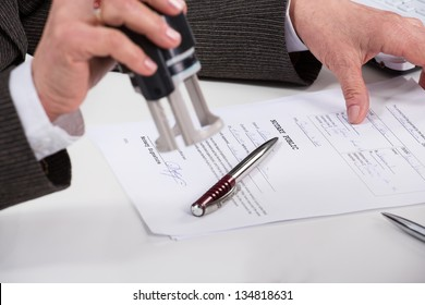 Notary public signing document at his workplace