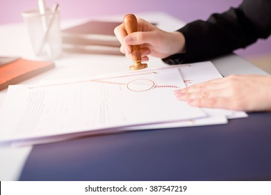 Notary Public stamping the document. Law office concept.