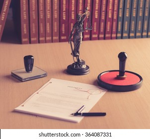 Notary public tools. Themis with scales of justice and notarial acts in the background.