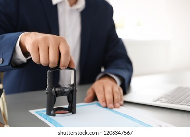 Notary stamping document at desk in office, closeup