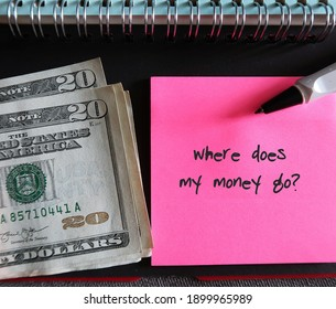 Note book, cash dollars money, pen, pink note with text written WHERE DOES MY MONEY GO?, concept of find out spending leaks to fix them and boost saving