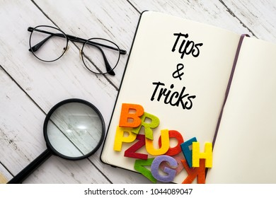 Note book and Magnifier over the white wooden board written TIPS AND TRICKS