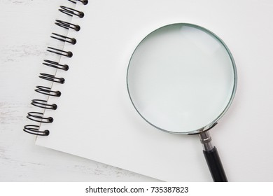 note book on white table with magnifying glass