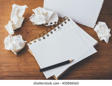 note book and pencil with crumpled paper on wooden background