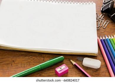 Note book, pencil, wood color, eraser, paper clip, pen, wood table.