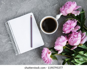 note book with peonies and cup of coffee on a stone background