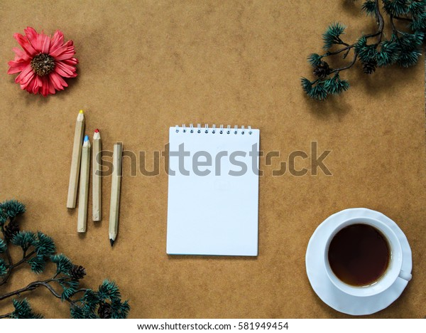 Note book, some wooden pencils and cup of coffee in the corner surrounded by dry red flower and branches of birch. Top view. Flat lay.