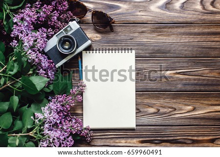 note book sunglasses camera and lilac flowers on wooden rustic background top view. spring picture with space for text. travel and wanderlust flat lay. planning summer or spring vacation