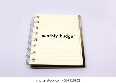 a note book with a text of monthly budget written on it