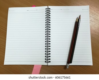 Note book with two pencils on a wooden desk