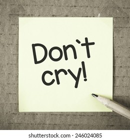 Note with don't cry. Note with don't cry and pencil on grunge background