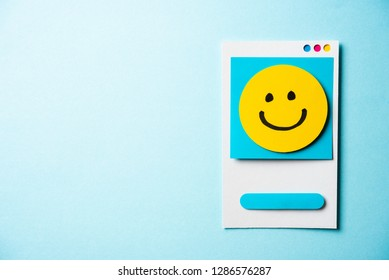 Note with happy smiling face cartoon and paper card concept on blue background. Happy work day concept.