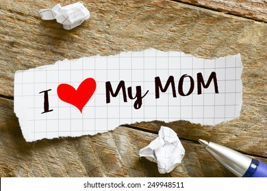Note with I love my mom. Note with I love my mom and red heart on the wooden background with pen