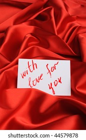 """Note on red silk. With an inscription """" With love for you """". Drawn by lipstick"""