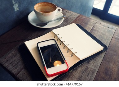 Note pad with smart phone in coffee shop