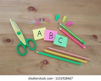 Note pads with ABC letters, colored pencils, paper clips and erasers laying on a wooden table, Back to school, School supplies, Writing and drawing utensils