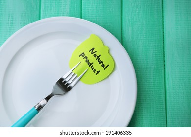 Note paper with message  attached to fork, on plate, on color wooden background