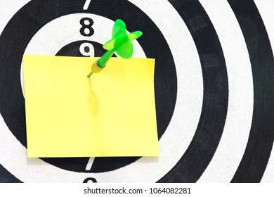 Note paper with steel tip darts to target. Empty paper sheet on dartboard game background. you can cut and paste text message on notepad.