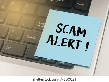 note paper written scam alert over keyboard button background