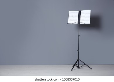 Note stand with music sheets near grey wall indoors. Space for text