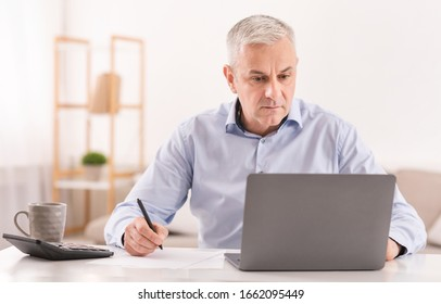 Note Taking. Attentive mature man writing details on paper and working on laptop, copyspace