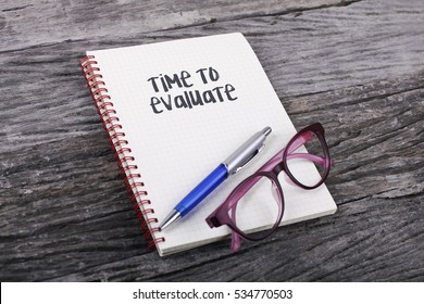 Note with Time To Evaluate on the wooden background